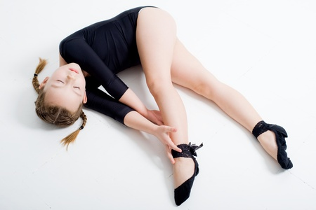 small pretty girl doing gymnastics over white background photo