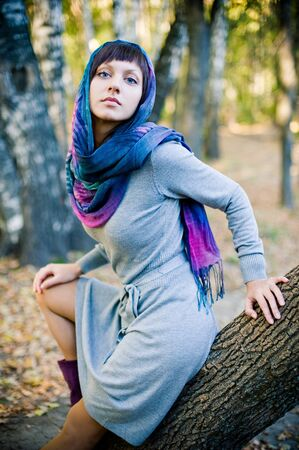 The girl in a scarf and in a knitted dress sits on a tree