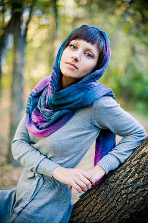 poses de modelos: La muchacha en una bufanda y con un vestido de punto se sienta en un árbol