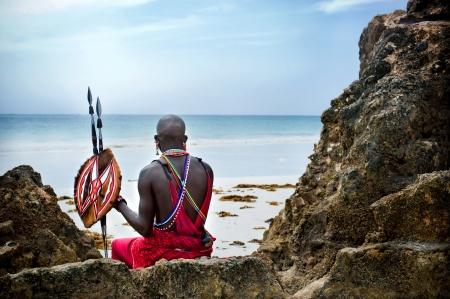Maasai sitting by the ocean on the beach