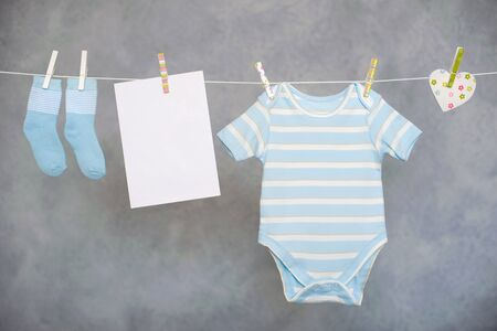 Blue baby goods and blank note hanging on the clothesline Imagens