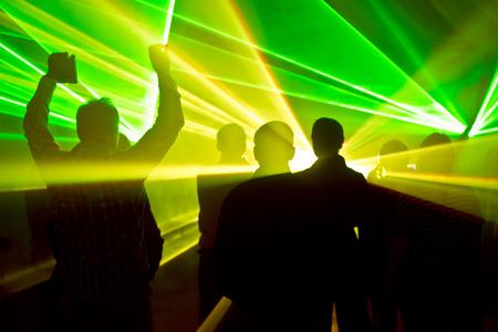 lasers in een nachtclub en silhouetten van dansende mensen