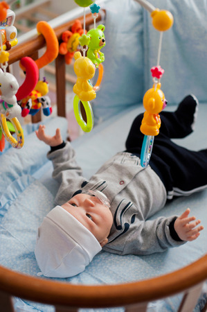 dressed baby lying in bed playing with a toy