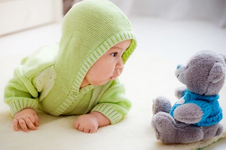 baby lying down looking at toy bear Standard-Bild