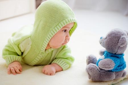 Bambino sdraiato guardando orso giocattolo Archivio Fotografico - 35754212