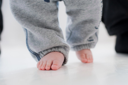 baby steps with the help of his father. white background