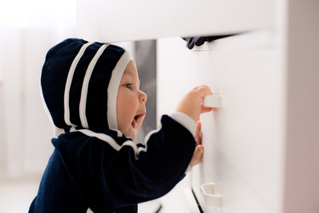 curious baby opens white linen closet.  Risks