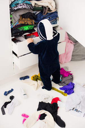 child throws the clothes out of the closet on the floor