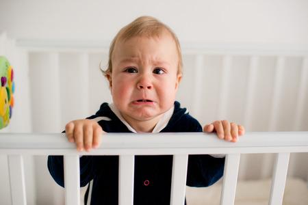 caras graciosas: El beb� llora y llama a mam� de una cama Foto de archivo