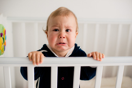 The baby cries and calls mom from a bed Stock Photo - 35892118