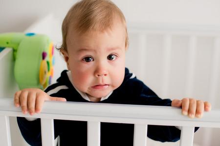 ojos tristes: El beb� llora y llama a mam� de una cama Foto de archivo