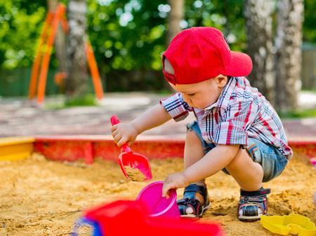 乳幼児: 子供のおもちゃの車をサンド ボックス内で再生