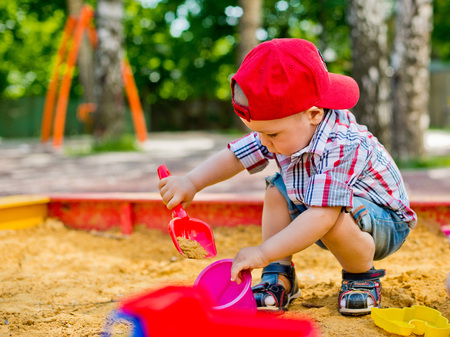baby playing toy: child playing in the sandbox with toy car Stock Photo