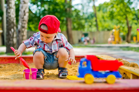 child playing in the sandbox with toy car Stock Photo