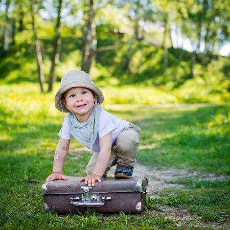 climbed: small child in a headdress playfully climbed a suitcase
