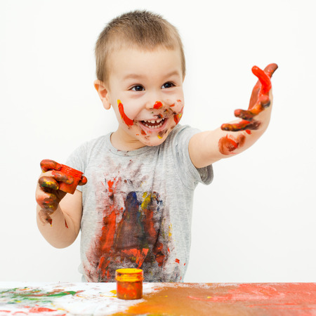messily: little boy covered in paint on a white background