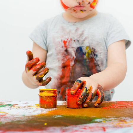 smeared hand: little boy covered in paint on a white background