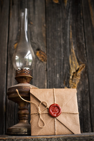 love letter and an old oil lamp on a wooden background