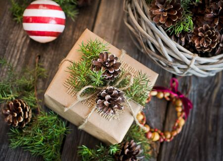 ECO: gift decorated with pine cones on the wooden background