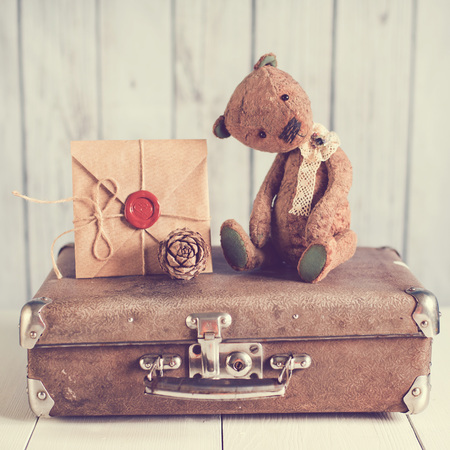 Teddybär auf einem Koffer mit einem Liebesbrief Standard-Bild - 50132961