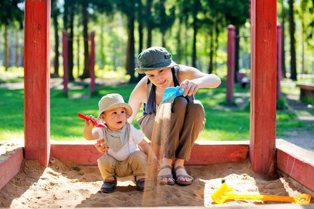 playgroup: Mom plays with the child in a sandbox in a park