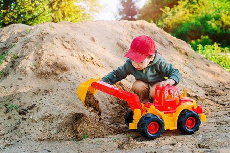 boy unloads sand on the toy excavator Stock fotó