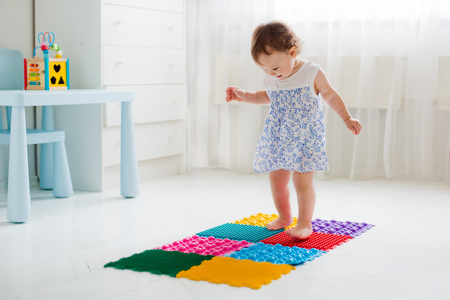 flatfoot: little girl walking on massage Mat