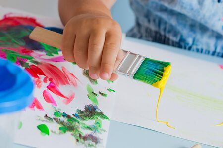 Brush with paint in the childs hand Banco de Imagens