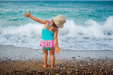 baby op het strand kijken naar de zee Stockfoto