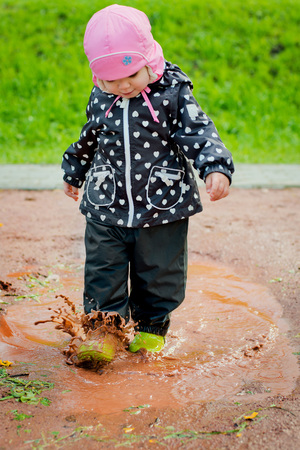 the child goes through the puddles Stock Photo