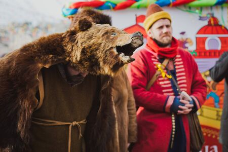 Russia. Moscow.Red square 26 Feb 2017. Carnival Maslenica . disguised in the skin of a bear entertains people on the street