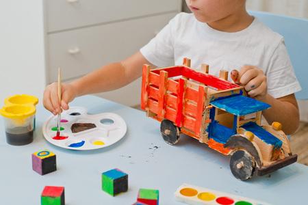 child paints a wooden typewriter