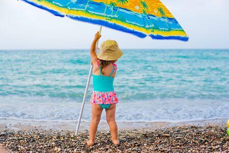 Child on beach under an umbrella
