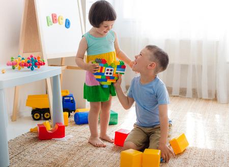 Un niño y una niña sostienen un corazón hecho de bloques de plástico. Hermano y hermana se divierten jugando juntos en la habitación. Niños en edad preescolar y juguetes educativos. Foto de archivo