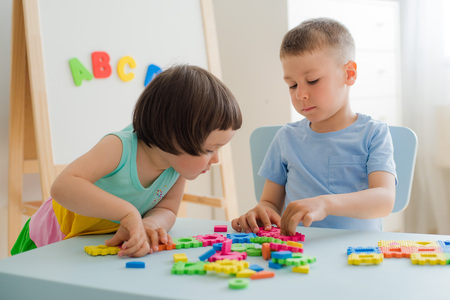 A boy and a girl collect a soft puzzle at the table. Brother and sister have fun playing together in the room. Preschool children and educational toys