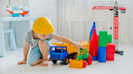 Small child 4 years old, playing with a large number of colorful plastic toys in the room, the construction of various facilities and trucks Stock Photo