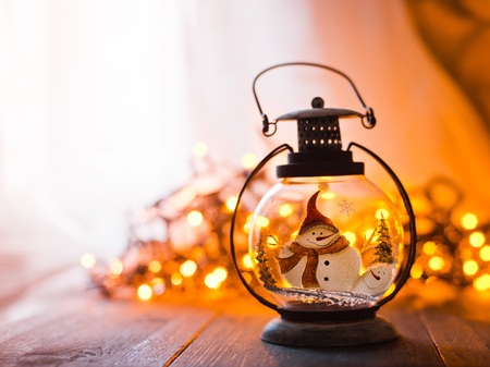 glass lantern with burning candles Christmas presents and a glowing garland on a wooden table. free space for text and congratulations. mocap