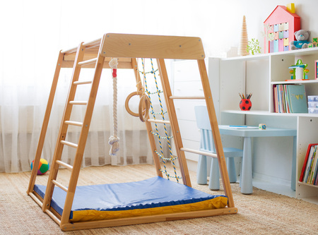 Childrens room with a wooden sports complex with stairs, rings and a rope. Childrens sports exercises. Physical education for children at home. Stock Photo