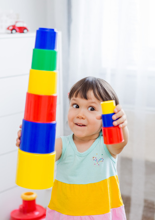 Happy preschool age children play with colorful plastic toy blocks. Creative kindergarten kids build a block tower. Educational toys for toddler or baby. Focus on little girl.