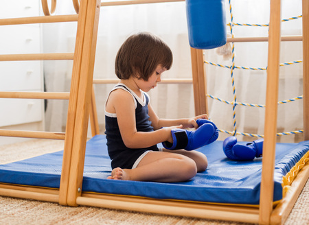A small child is engaged in boxing on a wooden home sports complex. Girl in boxing gloves hits the pear. Childrens physical development. Stock Photo
