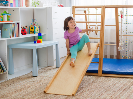 little girl having fun riding a roller coaster on a wooden home sports gaming complex stairs, rings and rope. Childrens sports exercises. Physical education of children at home.