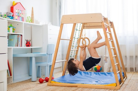 little girl performs gymnastic exercises on a wooden home sports complex stairs, rings and rope. Childrens sports exercises. Physical education of children at home.