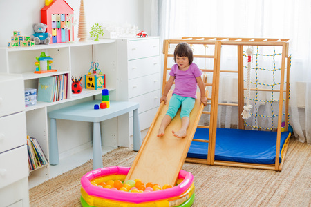 little girl having fun riding a roller coaster on a wooden home sports gaming complex stairs, rings and rope Dry pool with balls Childrens sports exercises. Physical education of children at home. 스톡 콘텐츠