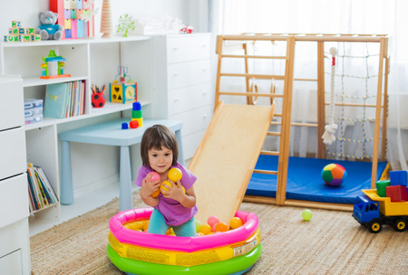 little girl having fun riding a roller coaster on a wooden home sports gaming complex stairs, rings and rope Dry pool with balls Childrens sports exercises. Physical education of children at home. Stock Photo