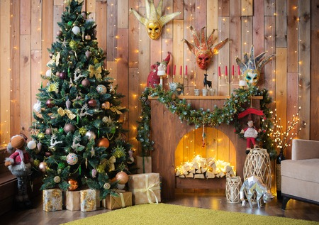 Christmas and New Year decorated the interior wooden room with gifts and a Christmas tree with a fireplace and carnival masks. Archivio Fotografico
