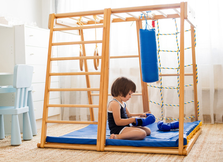 A small child is engaged in boxing on a wooden home sports complex. Girl in boxing gloves hits the pear. Childrens physical development. 스톡 콘텐츠