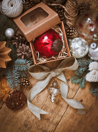 Christmas decorations on fir-tree branches and gifts on wooden background