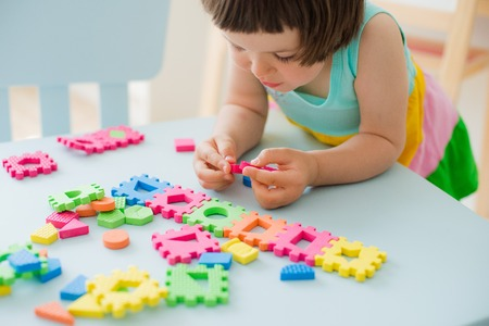 little girl playing at a childrens table with a puzzle, early education. Bright soft blocks