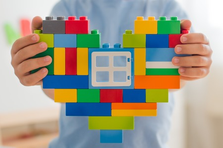 Plastic toy blocks, designer of childrens toys. Bright building blocks in the shape of a heart in childrens hands. Educational toys. Early learning. Concept of love. Window to the heart. beneficence