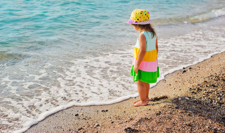 girl playing on the beach on summer holidays. Children in nature with beautiful sea, sand and blue sky. Happy kids on vacations at seaside running in the water. travel
